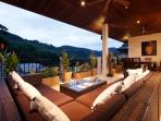 Undercover balcony with tranquil valley views and soft seating to relax in the evening
