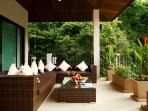 Undercover balcony with tranquil valley views and soft seating and stairs to swimming pool