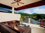 Large outside covered balcony with soft seating area to relax and enjoy the peaceful view