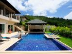 Large sun deck and swimming pool with integral Jacuzzi, feature swim platform and ample sunbeds