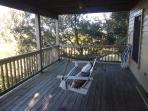 2nd level open air deck with porch swing and hammock