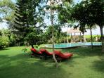The swimmingpool with longchairs under the trees
