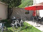Giardino esterno con barbecue, fontana, tavolo e ombrelloni