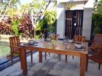 spacious outdoor entertainment area, surrounded by tropical garden