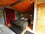 A sleeping hut bedroom has beds for 3 people and a separate toilet