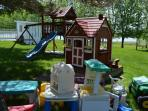 Kids playground with swings, slide, chalet with other outdoor toys