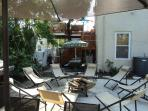 Patio in back yard with view to 2nd floor deck, fire bowl, etc.