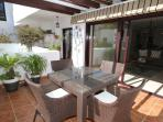 Sunny balcony with retracting overhead blind. Two  sun loungers.      Table/chairs, mountain views.