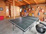 Double car garage with ping pong table, darts and a charcoal BBQ.