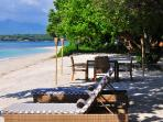 the private beach in front of the villa with sun loungers and dining table