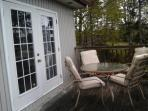 Garden doors out to deck with outdoor dining for four