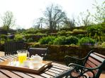 Breakfast on the terrace with raised beds and wooded fields behind.