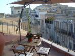 Terrazzino con sedie , tavolino, sdraio e ombrellone