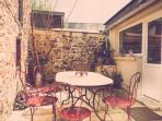 Et une terrasse fermée avec salon de jardin et barbecue