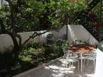 The sunny backyard with a nice table to have your breakfast in a Mediterranean style.