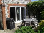 French doors from sitting room, patio area with barbeque and seating