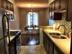 Beautiful kitchen with stainless steel appliances, quartz counters, tile floors, and new cabinets.