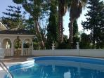 View of private swimming pool area & gazebo surrounded by palm and pine trees and landscaped gardens