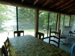 Screened porch with ample seating for dining and lake view