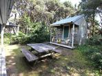 Small grassy backyard with deck, charcoal BBQ and picnic table.