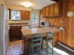 Fully equipped kitchen with all appliances and a breakfast bar for two.