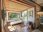 Sun room off living area with beautiful views, couch, wicker chairs and two sliders leading out to dual sided deck.