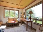 Master bedroom with a Queen bed, wicker couch, and large picture windows providing spectacular bay views.
