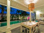 Dining area, lounge area and swimming pool at nightfall