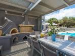 Fully equipped barbecue with wood oven, sink and dining area under the pergola