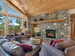 River rock fireplace, flat screen television and seating areas for gathering