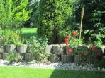 garden with grass, granit plates, natural stones, flowers