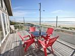 Large upper level ocean facing deck with table for four and extra patio chairs.