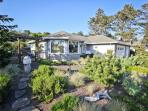 Front of Truly a Treasure from the road.  Beautifully landscaped yard with stone walking paths and a large gated in...