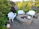 Beautiful gated landscaped side patio with fire pit, benches and a gas BBQ.