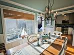 Nautical dining area with a table for 6, door to landscaped patio.