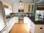 Fully equipped kitchen with stainless steel appliances and breakfast bar for three.  Opens into family room.