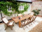 Large oak-sleeper table surrounded by grapevines