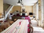 de woonkamer met haard en zetelbed onder de trap