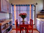 Eating area in light-filled kitchen with pretty red and blue accents
