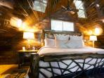 The loft bedroom features a king-sized bed in a wooden log frame.