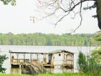 Peer with covered deck, boat house, and sundeck