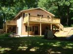 Back of Lodge - deck is entered from a queen and a king bedroom on main level. Below deck is hot tub