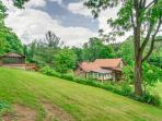 Appreciation of cabin and hot tub area within a secluded, quiet, and green setting.