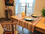 Dining table in the main room with 2 arm chairs and 2 folding wood chairs