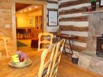 from DR to LR. Original logs, stone fireplace, antique farm table & custom built chairs