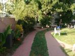 Quaint brick walkway to guesthouse with tropical plants
