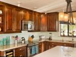 Glass tile backsplash, large island, henkle knives etc -  a true gourmet kitchen