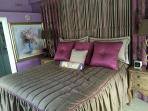king bedroom with luxurious bed linens and decor