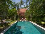 Large swimming-pool set in tropical garden leading up to second bedroom pavilion