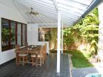 Terrace with dinner table and view of pool and gazebo